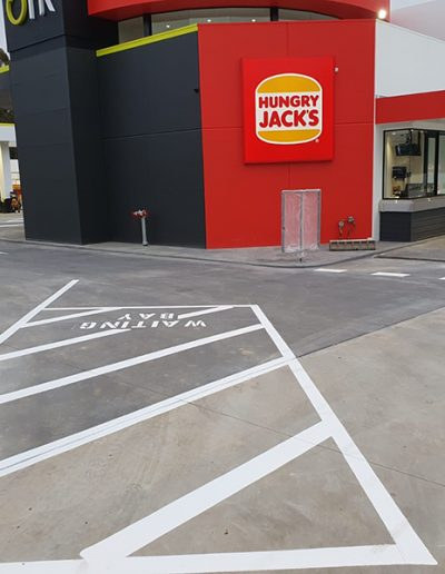 A newly marked Hungry Jacks drive thru, waiting bay and carpark with directional arrows.