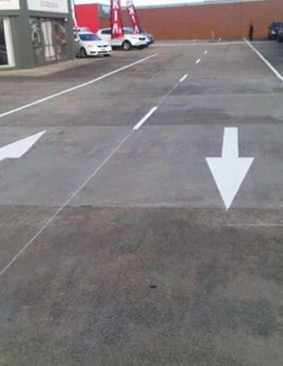 Directional arrows and lane markings on the road around a Kia Motors car yard.
