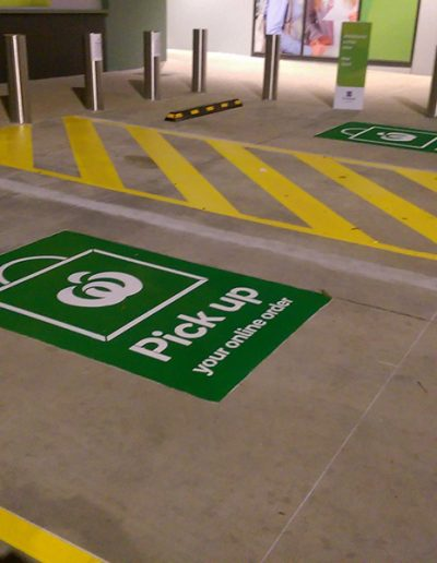 Two Woolworths carparks outside a shopping centre for customers to park when collecting online orders. Two carparks have a walkway painted between them and a sign in the middle of each with the Woolworths logo and Pick up your online order.